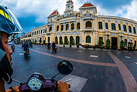 A motorscooter turns in front of the Hotel de Ville (Ho Chi Minh City Hall), Ho Chi Minh City (Saigon), Vietnam.