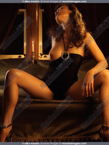 Beautiful half naked woman sitting on a bed at night