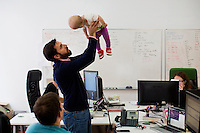 Mike Gutner (center), who handles operations at Mimo, his 10-month-old daughter Sadie Gutner as he speaks with Thomas Lipoma, Mimo co-founder and co-CTO, the Mimo headquarters Boston, Massachusetts, USA, on Mon., April 28, 2014. Sadie, daughter of Mike Gutner, is wearing one of the company's onesies, made by Mimo, which has a variety of sensors on it. The onesie has a detachable frog-shaped communication device that transmits data from the onesie's sensors and sends the data to a smartphone app, which displays information about the baby's respiration, skin temperature, position, and activity level. The onesie is washable and the device is water-resistant.