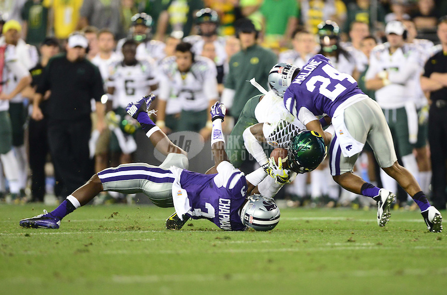 Jan. 3, 2013; Glendale, AZ, USA: Oregon Ducks wide receiver Josh Huff (1) is tackled by Kansas State Wildcats defensive back Allen Chapman (3) and defensive back Nigel Malone (24) during the 2013 Fiesta Bowl at University of Phoenix Stadium. Oregon defeated Kansas State 35-17. Mandatory Credit: Mark J. Rebilas-