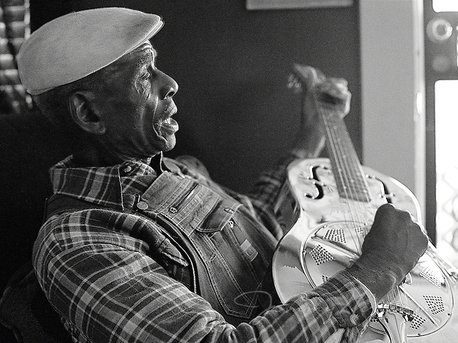 African-american Blues Musician, John Dee Holeman, plays his guitar and sings inside his home in Durham.