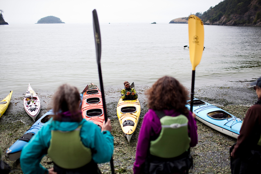 A group of people watch as an instructor demostrates some kayaking skills on the beach at Deception Pass State Park, WA, USA.