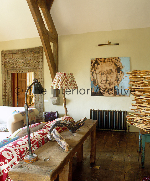 View over a rustic wooden console table to an abstract portrait in the living room