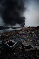 E-waste litters the ground while a huge fire burns at Agbogbloshie dump, which has become a dumping ground for computers and electronic waste from all over the developed world. Hundreds of tons of e-waste end up here every month. It is broken apart, and those components that can be sold on, are salvaged. Burning creates some of the most carcinogenic and toxic substances known, including polycyclic aromatic hydrocarbons, dioxins and furans, as well as releasing toxic metals such as lead, beryllium and cadmium. At theses burning sites concentrations of toxic metals have been found at over one hundred times the normal level.