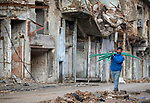 A man carries plastic pipes past damaged buildings in the old city of Mosul, Iraq. This portion of the city was heavily damaged in 2016 and 2017 when Iraqi forces, supported by U.S. air strikes, combated Islamic State fighters who held residents of the old city as human shields.
