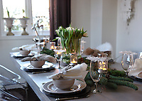 The dining table is laid for Christmas dinner, its spruce branches, flowers and linen napkins creating a rustic, fresh feel to the traditional meal