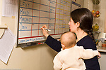 Day Care Center female caregiver holding infant making schedule note on dry erase board
