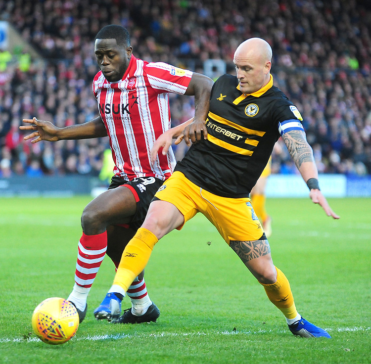 Lincoln City's John Akinde battles with  Newport County's David Pipe<br /> <br /> Photographer Andrew Vaughan/CameraSport<br /> <br /> The EFL Sky Bet League Two - Lincoln City v Newport County - Saturday 22nd December 201 - Sincil Bank - Lincoln<br /> <br /> World Copyright © 2018 CameraSport. All rights reserved. 43 Linden Ave. Countesthorpe. Leicester. England. LE8 5PG - Tel: +44 (0) 116 277 4147 - admin@camerasport.com - www.camerasport.com