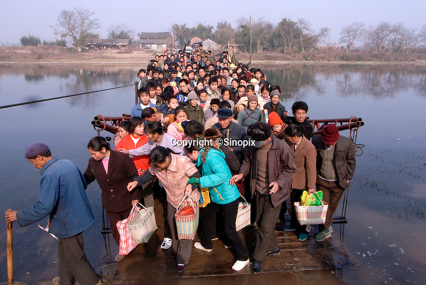 A crowd packs a ferry on the last market-day before the Chinese New Year in Quanzhou, Guangxi Province, China. The New Year Eve's dinner is traditionally the most sumptuous meal of the year. .26 Jan 2006
