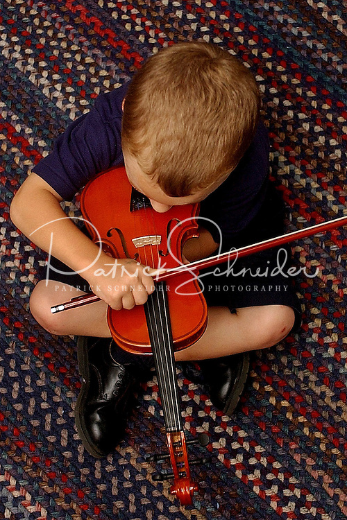 A young boy tries his hand at playing a child-size violin.