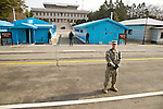 Republic of Korea (South Korea) soldiers stand guard with a US solider in the foreground at the Joint Security Area in between North Korea and South Korea in the village of Panmunjom on March 15, 2013.   Tensions have been steadily rising since North Korea detonated a nuclear device in February.  The United States has repositioned several military assets in support of South Korea.