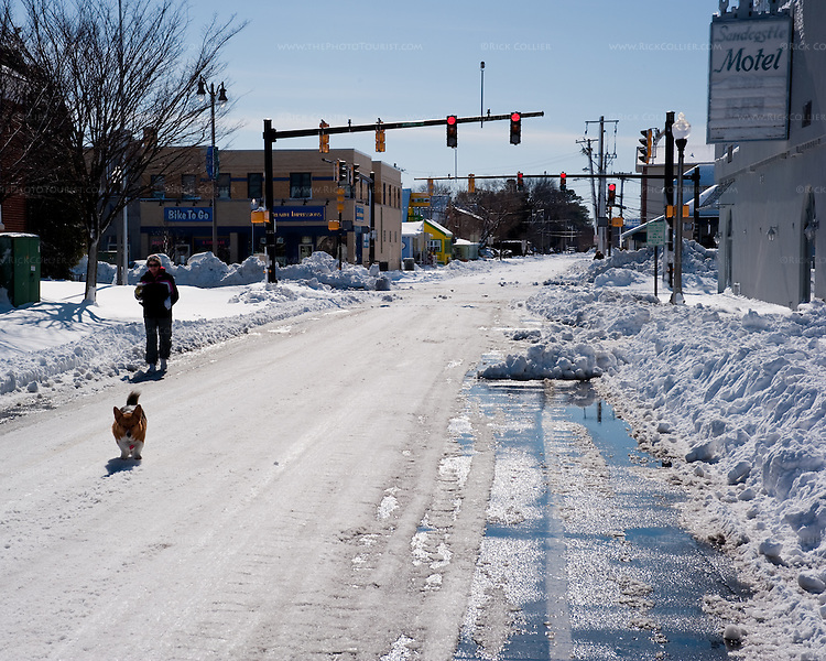 With the sidewalks piled high with snow, pedestrians walk along the snowy Rehoboth Avenue in Rehoboth Beach, Delaware, USA, the morning after the blizzard of February 2010.