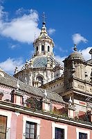 The church spire of the Church of El Salvador in Seville, Spain rises above newer apartment buildings.