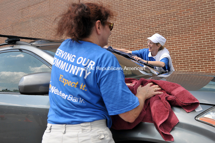 WATERBURY, CT - 24 July 2012-072412EC05--    Carol Olson (L) of Waterbury and Jane Cabot of Southbury (R) wipe down a car at Webster Bank in downtown Waterbury Tuesday morning.  Olson is the Manager of Operations at the bank, and joined a dozen other employees to host a car wash in the parking lot to benefit the United Way.  Erin Covey Republican American.