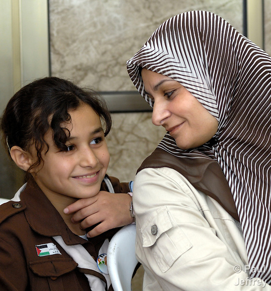A mother in Gaza talks with her daughter, who is a member of the Girl Scouts. Both live in the Beach Refugee Camp.