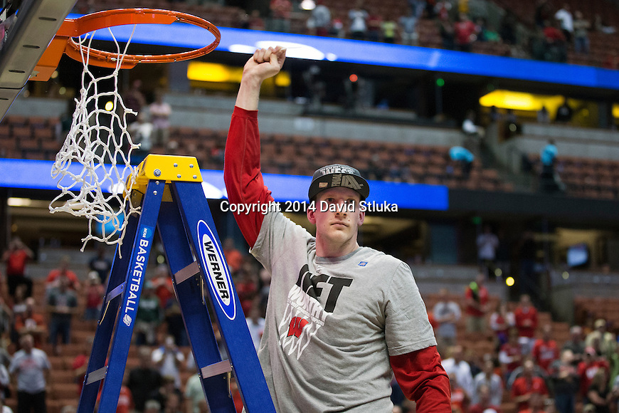 Wisconsin Badgers Evan Anderson cuts down a piece of the net after the Western Regional Final NCAA college basketball tournament game against the Arizona Wildcats Saturday, March 29, 2014 in Anaheim, California. The Badgers won 64-63 (OT). (Photo by David Stluka)
