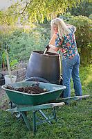 Gardener gathering fresh compost from compost bin, from tumbler to wheelbarrow