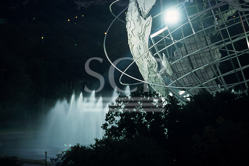 Flushing Meadows, New York, USA. 1964 Worlds Fair Unisphere in Corona park at night with electric lighting.