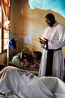 TANZANIA, Korogwe, village Kwalukonge, KWALUKONGE HEALTH CENTRE / TANSANIA, Korogwe, KWALUKONGE HEALTH CENTRE, Krankenhaus der Rosminian Fathers und Usambara Sisters in Kwalukonge, Father Ambrose Chuwa spricht ein gebet fuer die Kranken