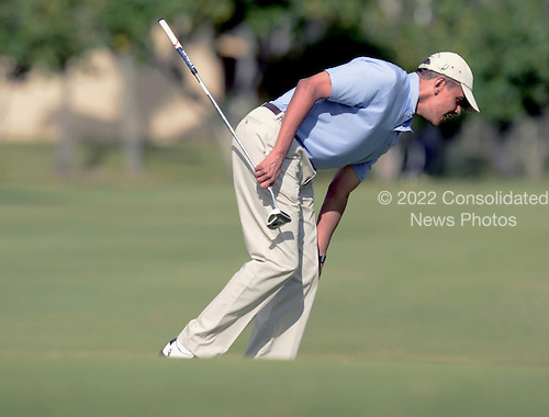 President Barack Obama reaches down to pick up his ball on the 2nd green while golfing with the Prime Minister John Key of New Zealand at Marine Corps Base Hawaii's Kaneohe Klipper Golf Course, Kaneohe, Hawaii, January 2, 2014. <br /> Credit: Cory Lum / Pool via CNP