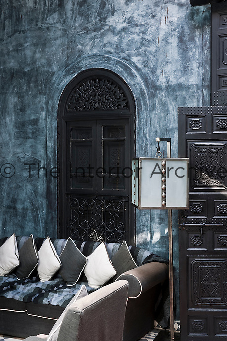 The living area of the Blue Apartment has bluey/black rag rolled walls and traditional Moroccan carved wooden doors
