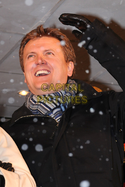 ALED JONES .Switches on the Christmas lights in  Basildon, Essex, England, UK, .18th November 2010.portrait headshot hand  arms crossed folded smiling striped scarf grey gray black .CAP/BRC.©Ben Rector/Capital Pictures.