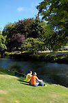 Couple sitting on the banks of the Avon River, Christchurch, New Zealand