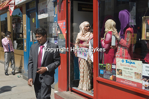 "Muslim women Brick Lane London wait for wedding guests to enter a resturant. The sign she holds reads ""No Money No Honey""' a tradition in Bengali wedding for the brides relatives to tease the groom into giving a small gift of money"