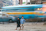 Two boys stand near a busy street, Kolkata, India