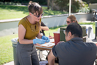 Emmons Student Wellness Center staff (Ann Martella, Cindy Bacon and Sylvia Rincon) give free flu vaccinations for students, faculty and staff on Oct. 7, 2014 in the JSC quad. The center will give the shots during three more clinics. (Photo by Marc Campos, Occidental College Photographer)