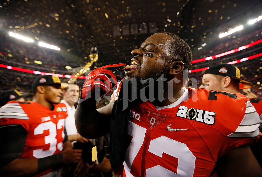 Ohio State Buckeyes defensive lineman Chris Carter (72) tastes a piece of confetti following their 42-20 win over Oregon in the College Football Playoff National Championship at AT&T Stadium in Arlington, Texas on Jan. 12, 2015. (Adam Cairns / The Columbus Dispatch)