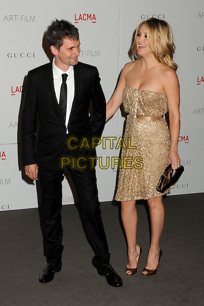 Matthew Bellamy and Kate Hudson.The Inaugural Art and Film Gala held at LACMA in Los Angeles, California, USA..November 5th, 2011.full length gold strapless dress clutch bag bronze beads beaded side black suit white shirt holding hands couple matt profile.CAP/ADM/BP.©Byron Purvis/AdMedia/Capital Pictures.