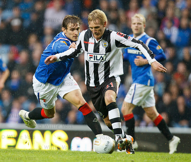 Gary Teale takes the ball away from Nikica Jelavic