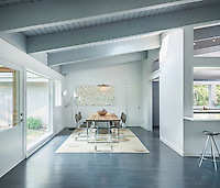A contemporary, spacious open-plan dining room with a grey painted beamed ceilling and a cerused oak floor. A full height door leads to the garden and allows plenty of light into the room.