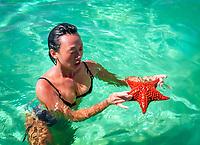 Dominikanische Republik, Frau im Wasser mit Seestern in der Hand | Dominican Republic, woman standing in water holding a starfish in hands