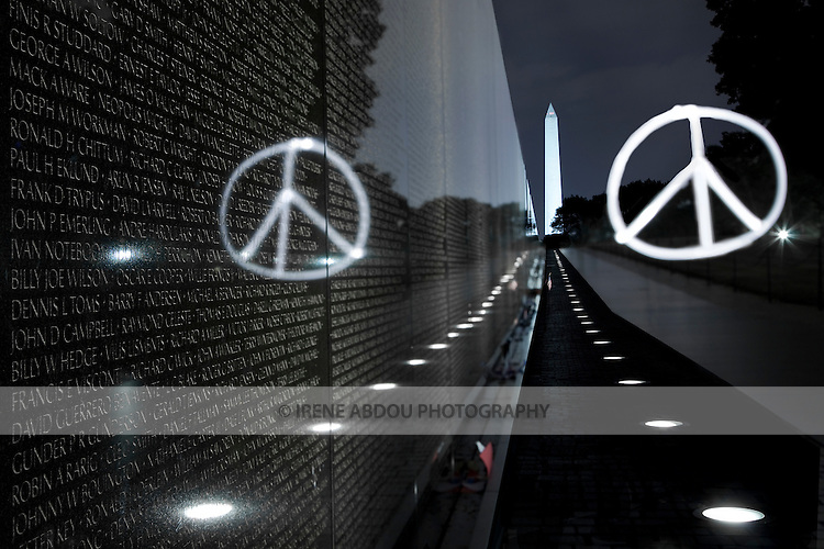 "Using a photographic technique called ""painting with light,"" the peace symbol is burned into the night at the Vietnam Memorial in Washington, DC, Washington monument in the background."