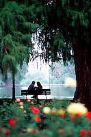 Romantic couple on park bench beside lake.