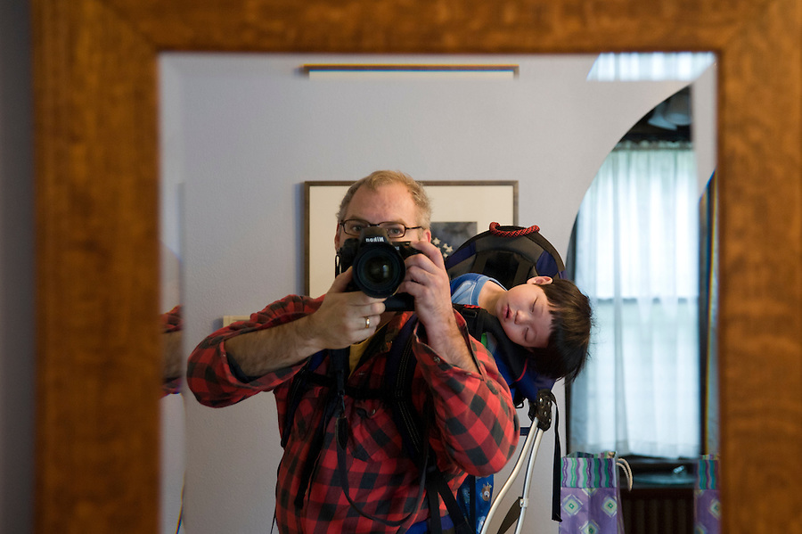 Standing in front of a mirror, photographer Jeff Miller makes a self-portrait while his 16-month-old son, Holden Miller, is slumped over and sound asleep in a backpack at the Miller/Stute home in Madison, Wis., on Oct. 24, 2008.