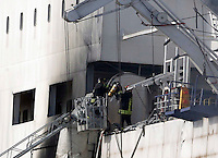 Firefighters stand on a ladder to inspect the Norman Atlantic multi-deck car-and-truck ferry docked at Brindisi harbour January 3, 2015.
