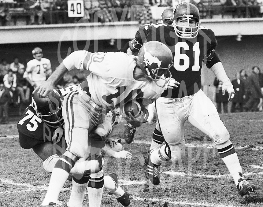 Charlie Brandon(61) and Wayne Smith(75) of the Ottawa Rough Riders tackle Calgary Stampeder quarterback Jerry Keeling 1972. Copyright photograph Scott Grant