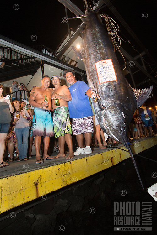 Bomboy Llanes (in blue shirt), captain of the fishing boat Lana Kila, stands with his crew next to a Pacific blue marlin grander at Honokohau Harbor, Kailua-Kona, Big Island.