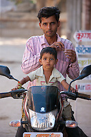 Indian man with child on a motorcycle in Narlai village in Rajasthan, Northern India