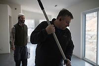 Sid Johnson, a licensed remodeler with Northwest Arkansas Floor Refinishing, (right) stains and seals concrete floor as Dave Bear, construction manager with Habitat for Humanity, (left) helps, Thursday, January 9, 2019 at a new home being built on 508 S. Washburn Ave. in Fayetteville. <br /> <br /> Habitat for Humanity is building their 57th house in Washington County for their Women Build program. In the program, women from the community come together to raise money for the building of a new home and also help build it. 70 percent of the home must be built by women.  <br /> <br /> The house will go to a single mother and her son. Habitat has partnered with local businesses to help build the house like Sid Johnson of Northwest Arkansas Floor Refinishing.<br /> <br /> Habitat has worked on the house since July and expects to finish by march. Habitat is looking for week day volunteers to help with construction. <br /> <br /> Anyone interested in volunteering can sign up on givepulse.com found through habitatwashingtoncoar.org. This year, Habitat will roll out a new home repair program. People will be able to apply to have their homes repaired based on need, paid for by an interest-free loan the home-owner would pay back. Check out nwaonline.com/200110Daily/ for today's photo gallery.<br /> (NWA Democrat-Gazette/Charlie Kaijo)