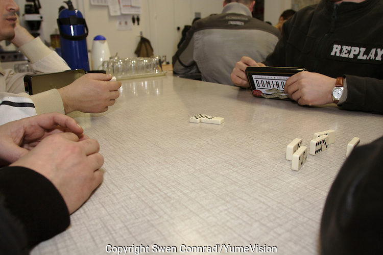 Domino party at the ARAVOH association, 200 meters reom the Vallorbe registration Centre of the Federal Office for Refugees (CERA)..The ARAVOH association was open in 2000 by a Christian priest and dozen of volunteers. He offer teas, coffees, biscuits, games, cloths, orientation to other organisations, institutions, associations and a basic psychological support.