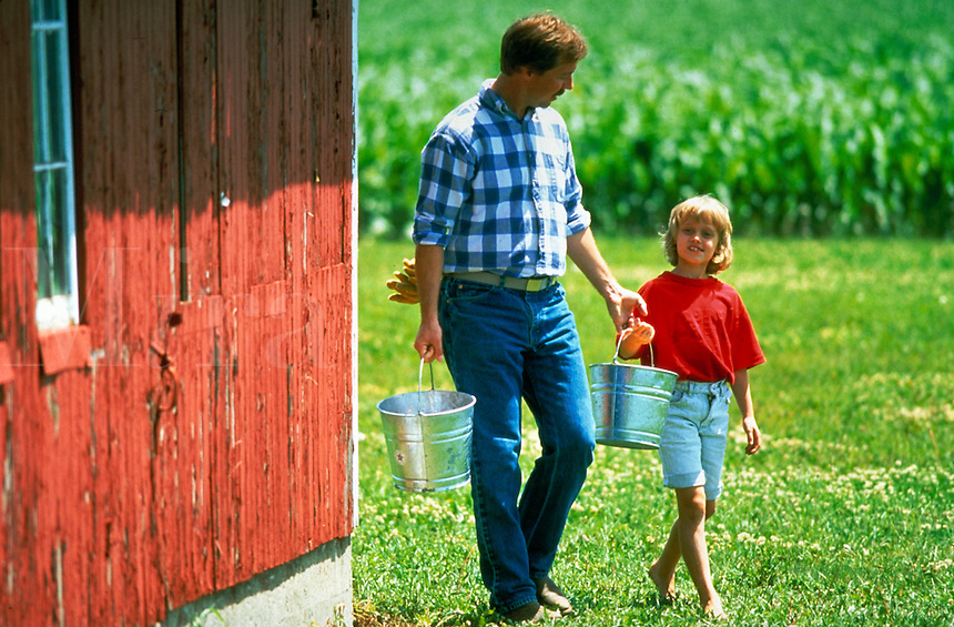 A farmer and his daughter do chores.