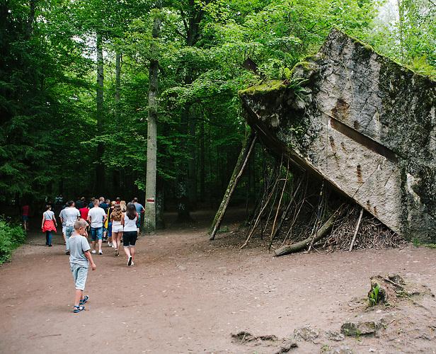 Touristen gehen an einer Bunkerruine vorbei. Es ist Brauch, Stöcke, die man im Wald findet, gegen die Mauern zu stellen und diese sinnbildlich abzustützen. / Tourists puttin down sticks they found in the woods, it's traditon at wolf's lair. / Wolfsschanze, Wolf's Lair