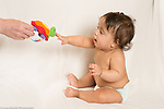 6 month old baby girl sitting in diaper keeping back straight as she reaches for toy held out for her