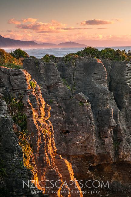 Pancake rocks and blowhole, limestone formations on rugged coast in Punakaiki during sunset, Paparoa National Park, Buller Region, West Coast, New Zealand, NZ
