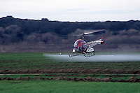 Aerial pesticide spraying on a field of agricultural crops.