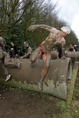 30 January 2005: A male competitor wearing only a pair swimming trunks jumps over the Anaconda obstacle during the Tough Guy Jungle Warrior vs Genghis Klan race held at Mr Mouse Farm for Unfortunates, South Perton, Staffordshire. The race is held twice a year on farm land over a army style assault course. Tough Guy is a physically challenging, mentally demanding, fear inducing, visually spectacular endurance race and is one of the worlds toughest events. Photo: Neil Tingle/Action Plus...050130 muddy mud crazy man men